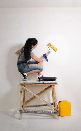 redecorating: Young girl crouched on a wooden trestle painting the wall while redecorating the house Stock Photo