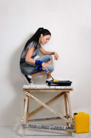 crouched: Handy young woman painting a wall in her house or apartment crouching balanced on a wooden trestle for extra height in front of a paint roller and tray