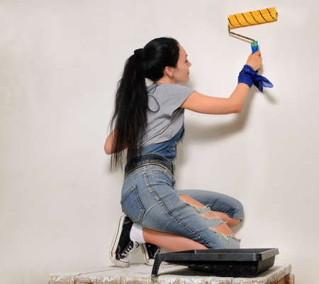 crouched: Young woman in trendy jeans with her brunette hair in a ponytail painting a wall with a roller during renovations Stock Photo