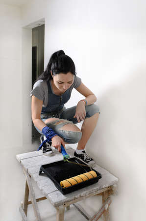 capable: Capable young woman painting a wall crouching balanced on a wooden trestle for extra height in front of a paint roller and tray Stock Photo