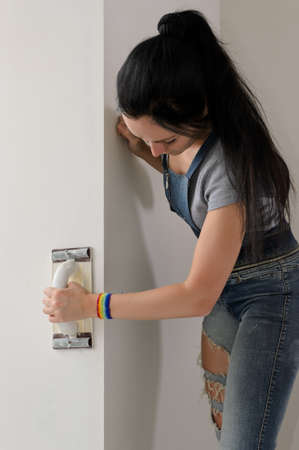 Young woman finishing off the surface of a wall as she prepares it for painting and redecorating photo
