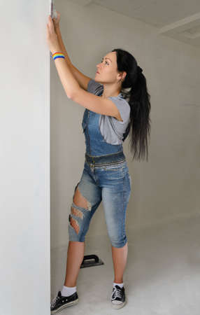 redecorating: Shapely young woman in trendy jeans redecorating her apartment stretching up the wall as she smooths the surface for painting Stock Photo
