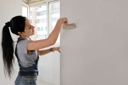 Woman painting an apartment wall finishing off the redecorating with a paintbrush