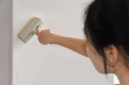Woman painting a wall finishing off the edges near the corner with a paint brush while renovating photo