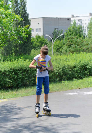 Young teenage female roller skater standing in her rollerblades putting on palm and wrist guards to protect herself in the event of a fall photo