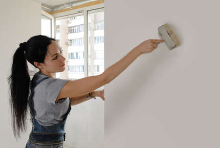 Attractive young woman redecorating her house painting a wall with a brush with copyspace