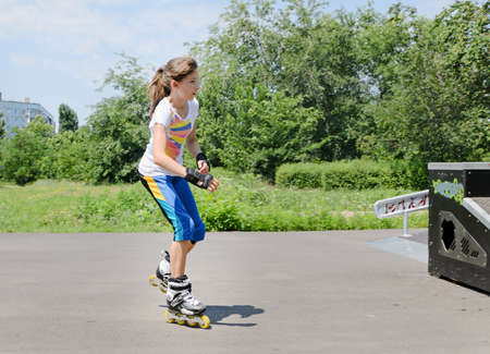 Pretty young teenage girl roller skating in her roller blades at a skate park in the summer sunshine photo