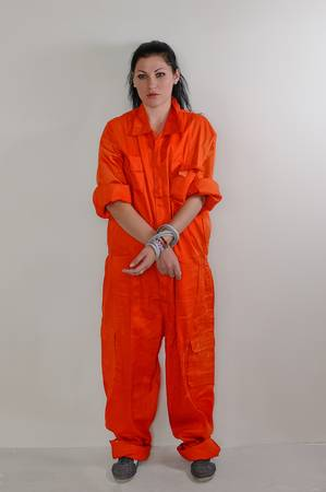 prisoner woman: Woman in orange overall with hands crossed