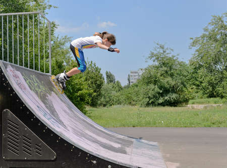 off ramp:  young teenager roller skating launching herself off a curved cement ramp