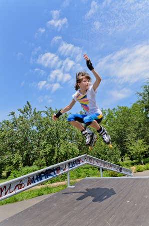off ramp: Agile young teenage girl roller skating jumping midair with her legs bent off a steep cement ramp
