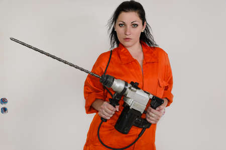 Competent woman with an electric masonry drill in her hands fitted with a very large long bit standing looking at the camera with a serious expression photo