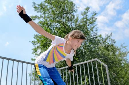 A cheerful teenage girl enjoying during skating practice in the park. photo