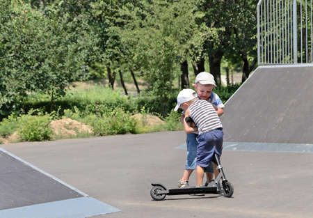 tussle: Two young brothers fighting over a toy scooter in a skate park having a tussle as to who will ride it next