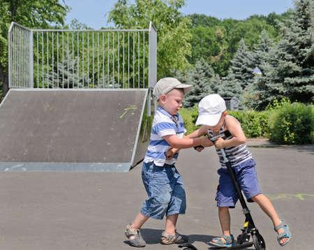 pull toy: Dos ni�os con gorras de b�isbol peleando por una vespa en un parque de patinaje como la intimida el otro para bajar