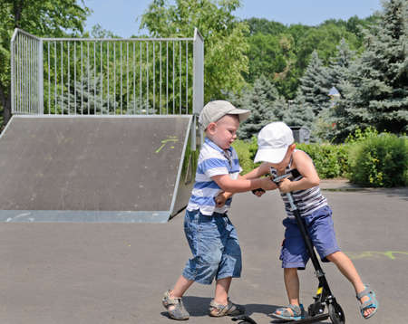 Two young boys in baseball caps fighting over a scooter in a skate park as the one bullies the other to get off