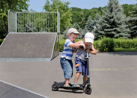 Two small boys standing arguing and fighting over who will get to ride a scooter in the skate park