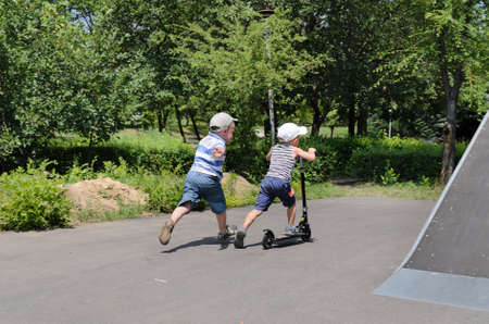 Two young boys playing with a scooter in a skate park with one riding and the other running alongside as he tries to catch him