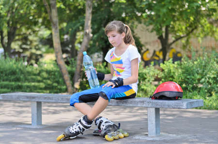 A teenage girl drinking water during skating break in the park. photo