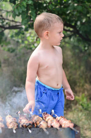 Young shirtless boy cooking barbecue standing over the smoking fire turning the grilling kebabs by hand photo