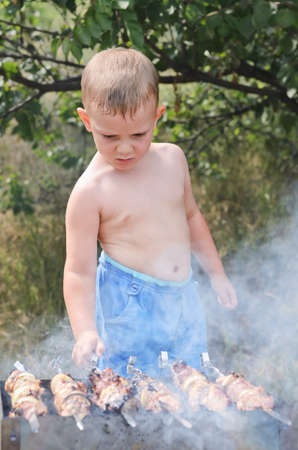 Young shirtless boy cooking at a barbecue standing over the smoking fire turning the grilling kebabs by hand photo