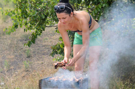 bending down: Attractive woman cooking meat on a barbecue bending down over the fire to test if it is ready to eat