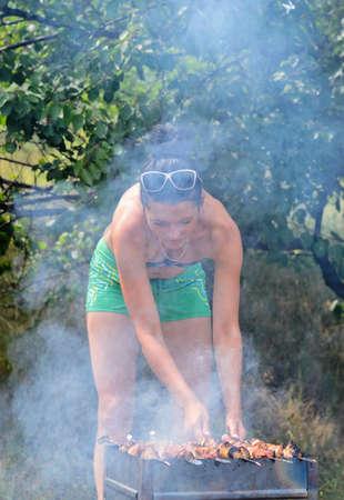bending down: Atractiva mujer de cocinar la carne en una barbacoa inclin�ndose sobre el fuego