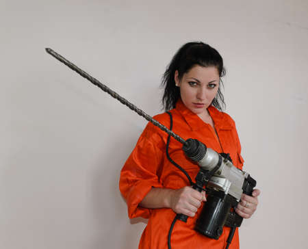 Woman in orange overalls holding an electric drill photo