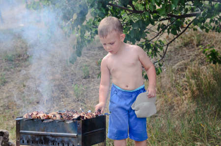 Little boy on his summer vacation standing shirtless turning kebabs photo