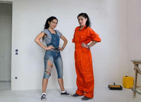 jambes �cart�es: Deux jolie jeune femme capable d'attitudes debout habill� pr�t � faire des travaux de r�novation de la maison avec leurs mains sur les hanches et les jambes �cart�es Banque d'images