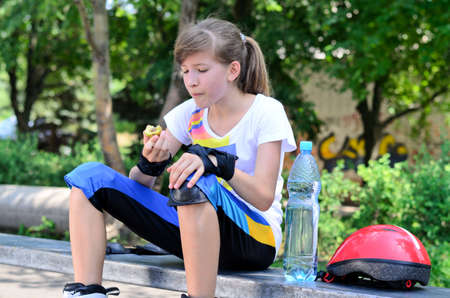 A sweet teenage girl taking a break, sitting and eating photo