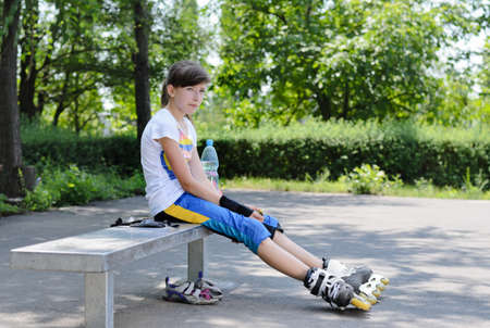 A cute teenage girl sitting and relaxing during skating practice in the park. photo