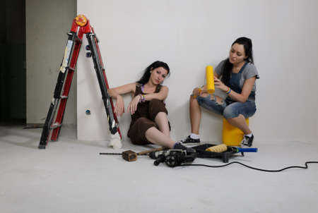 Two young women renovating a house taking a break sitting on the floor surrounded by all their tools and equipment and a stepladder photo