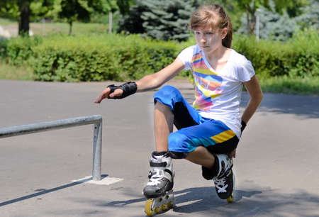 Attractive athletic teenage girl balancing on her rollerblades as she squats down level with asphalt photo