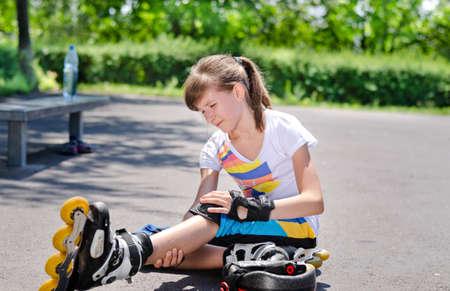 crick: Attraente giovane skater adolescente smorfia di dolore e di cura il suo ginocchio infortunato e la gamba dopo l'assunzione di una caduta sull'asfalto presso la pista di pattinaggio