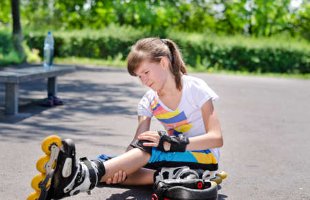 Young attractive teenage skater grimacing in pain and nursing her injured knee and leg after taking a fall on the asphalt at the skating rink Stock Photo - 21329719