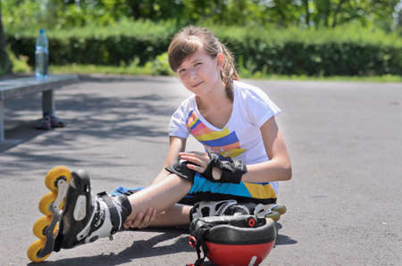 Young teenage roller skater sitting on the asphalt looking at her bruised arm after falling while practising photo