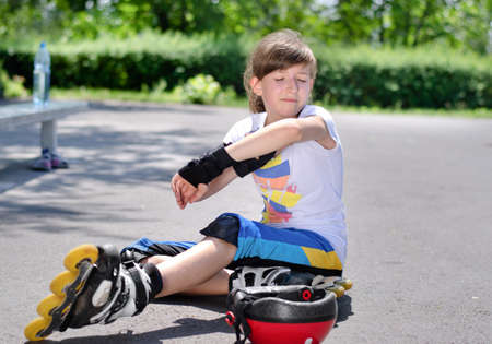 crick: Giovane ragazza seduta sulla pista skate park guardando il suo braccio contuso dopo l'assunzione di una caduta sui suoi pattini a rotelle Archivio Fotografico