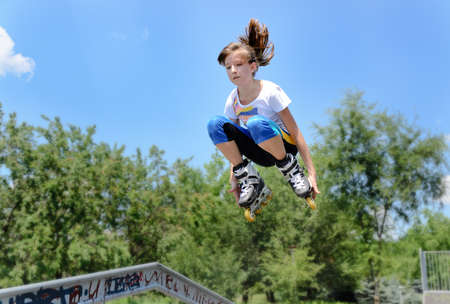 off ramp: Attractive young teenage girl jumping in the air on rollerskates as she jumps off a ramp at a skate park
