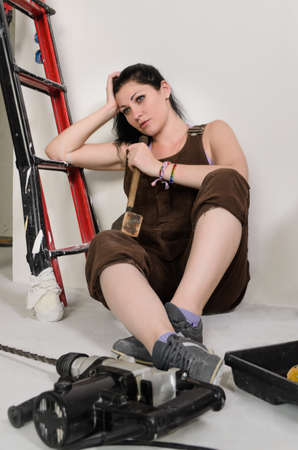 redecorating: Tired woman resting while redecorating sitting on the floor leaning on the stepladder with a despondent look