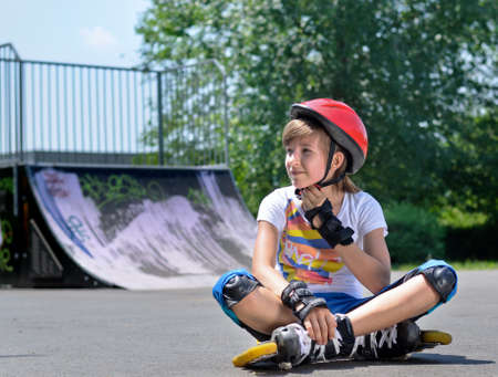 Pretty teenage girl in roller skating gear with a safety helmet, rollerskates and hand and wrist guards sitting waiting on the asphalt at a skate park