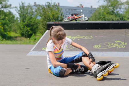 Young girl wearing rollerskates massaging her calf muscles as she sits on the ground at a skate park in front of a cement ramp photo