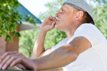 puffing: Trendy young man enjoying a smoke break sitting outdoors relaxing in the garden puffing on his cigarette , low angle close up view Stock Photo