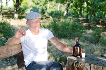 reefer: Man enjoying his vices sitting outdoors in woodland at a rustic table smoking a cigarette or reefer and drinking alcohol from a bottle