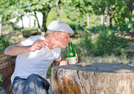 rueful: Man with a drinking problem sitting outdoors in a wooded park at a rustic table taking a swig of alcohol from a bottle