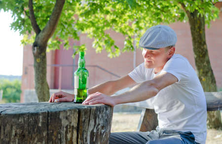 philosophical: Man enjoying a quiet drink outdoors sitting at a rustic wooden table in the garden with a large bottle of alcohol in front of him