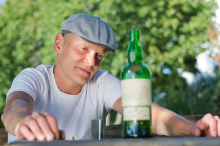 rueful: Portrait of a depressed middle-aged man sitting at the table in the garden looking at a bottle of white wine