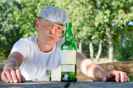 natty: Good-looking man wearing a natty cap with a drinking problem sitting at a table in the park staring morosely at his bottle of liquor standing on the table