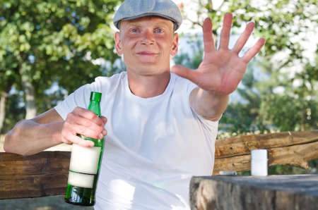 addictive drinking: Smiling drunk defending his bottle of alcohol sitting at a rustic wooden table outdoors with one hand extnded towards the camera in a halt gesture while clutching his bottle in the other Stock Photo