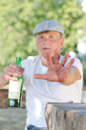 addictive drinking: Man giving the Stop or Halt gesture with the palm of his hand as he tries to ward off unwanted attention in the bottle of alcohol that he is drinking and holding in his hand