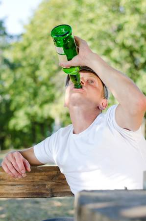 boozer: Boozer knocking back the alcohol gulping down the contents of a large green bottle of spirits as he sits outdoors in a park, low angle view